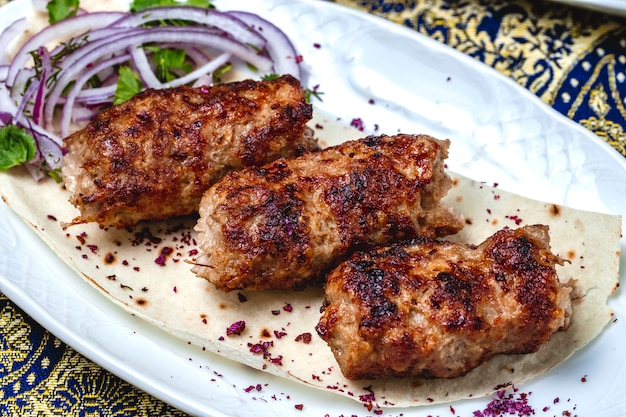 Kebab de lulya de vista lateral com verdes de cebola roxa e bérberis secas na pita
