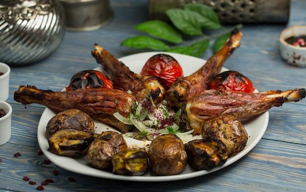Kebab de pepita de frango com batatas e tomates grelhados.
