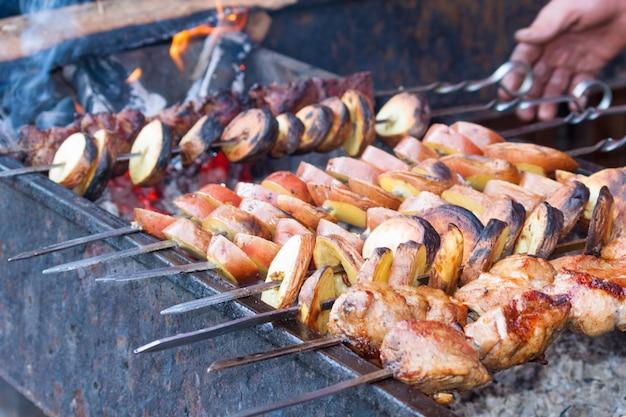 Kebab de shish com os potatos que roasting na grade. festa de churrasco.