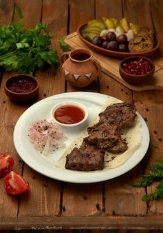 Kebab de vitela marinado servido com mistura de cebola e sumagre, molho de tomate e ervas