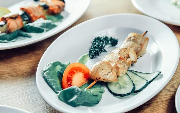 Kebab e legumes frescos em um prato branco sobre a mesa de uma loja de kebab