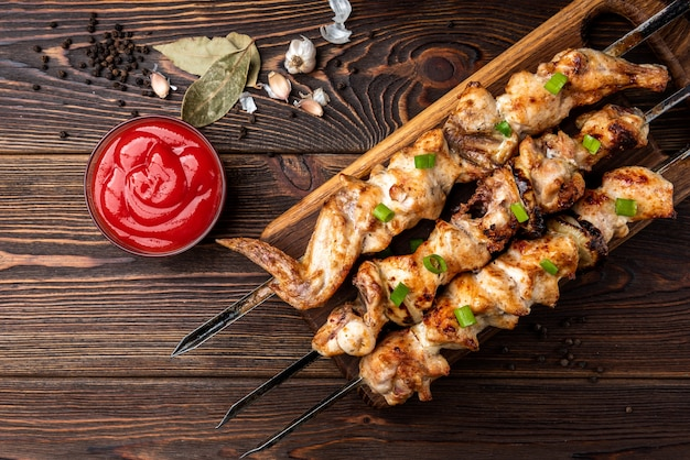 Kebab grelhado com ketchup e especiarias em fundo de madeira.