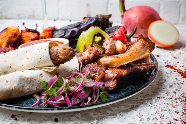 Kebab variado com legumes fritos e cebola em prato redondo