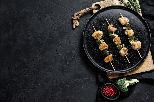 Kebabs - espetos de carne grelhada, shish kebab com legumes. fundo preto. vista do topo. espaço para texto