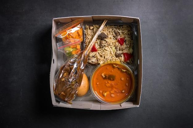 Kebuli rice satay caril de cordeiro e rendang com caixa branca sobre fundo preto caixa de arroz para aqiqah