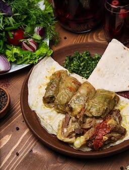 Kelem dolmasi, folhas de couve recheadas com carne e arroz, com ensopado de carne com legumes em lavash.