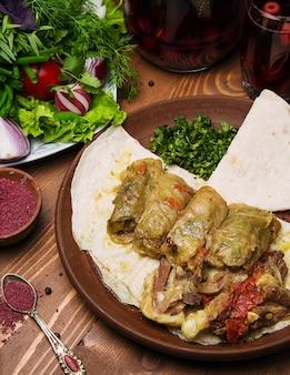 Kelem dolmasi, folhas de repolho recheadas com carne e arroz, com guisado de carne com legumes em panela.