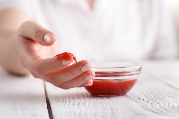 Ketchup de tomate de teste fêmea no dedo