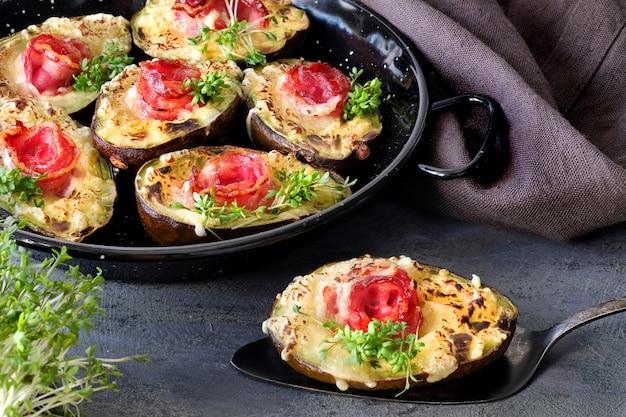 Keto dieta prato: abacate barcos com bacon crocante, queijo derretido e brotos de agrião no escuro