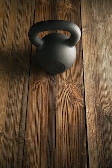 Kettlebell de ferro na mesa de madeira