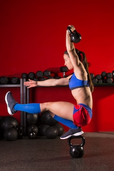 Kettlebell mulher pistola agachamento equilíbrio no ginásio