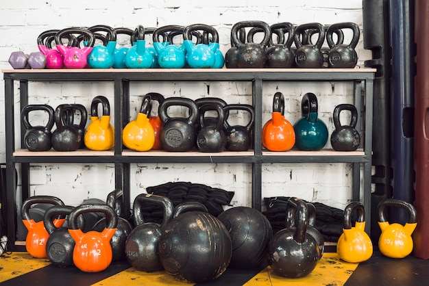 Kettlebells coloridos dispostos em rack