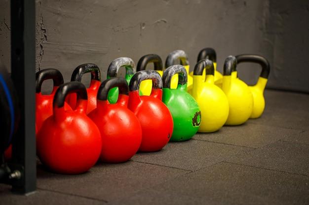 Kettlebells coloridos em uma fileira em uma academia. kettlebells de ferro pesado no chão do ginásio, prontos para exercícios de força e condicionamento.