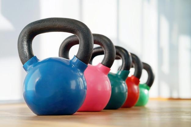 Kettlebells coloridos em uma linha em uma academia