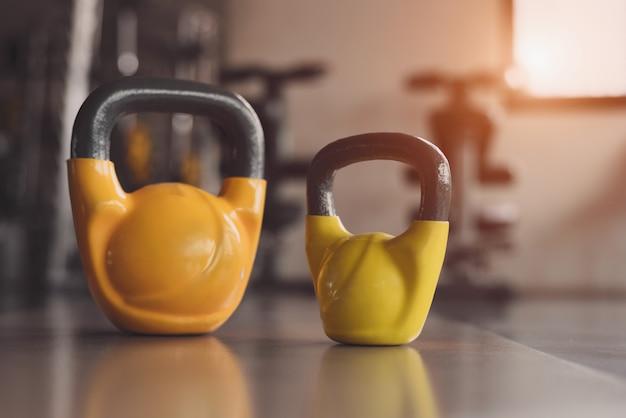 Kettlebells ou halteres no chão do ginásio de fitness. equipamento esportivo de peso pesado