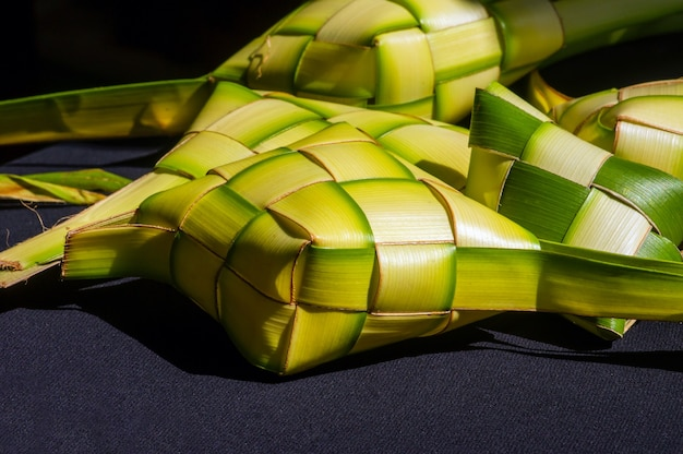 Ketupat, em fundo escuro, um bolo de arroz embalado dentro de um recipiente em forma de diamante com folhas de coco