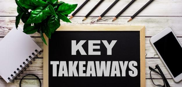 Key takeaways está escrito em branco em um quadro negro ao lado de um telefone, bloco de notas, óculos, lápis e uma planta verde