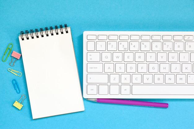 Keybord com caderno espiral em branco, caneta azul