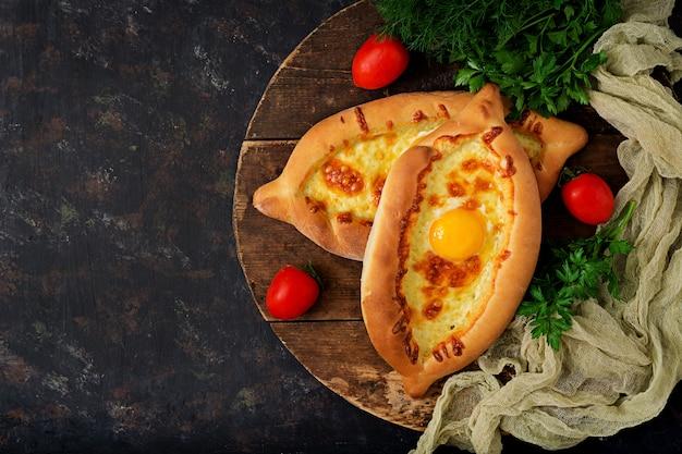 Khachapuri em adjário. torta aberta com mussarela e ovo. cozinha georgiana.