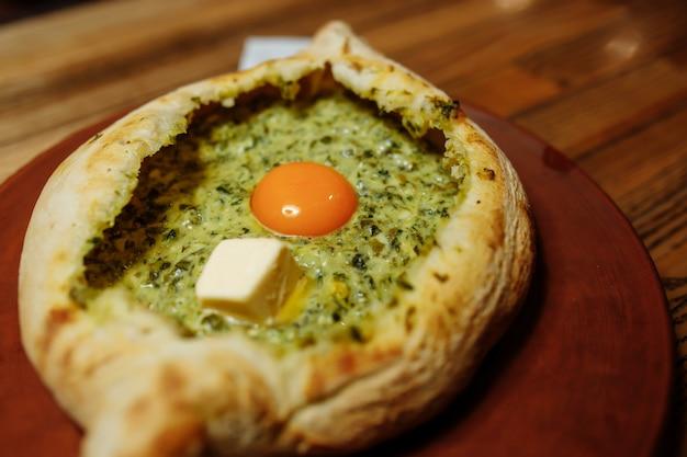 Khachapuri feito de uma deliciosa massa macia com espinafre, queijo derretido e manteiga close-up.