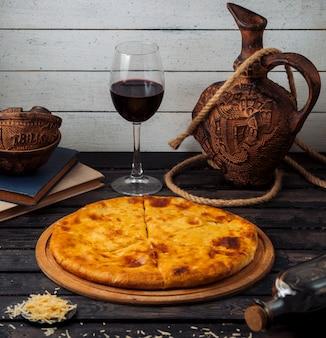 Khachapuri georgiano servido na tábua de pizza de madeira com vinho tinto