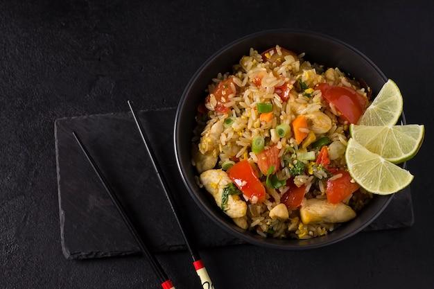 Khao pad, arroz frito com legumes, carne e ovos, com pepinos frescos, tomates, com pauzinhos.