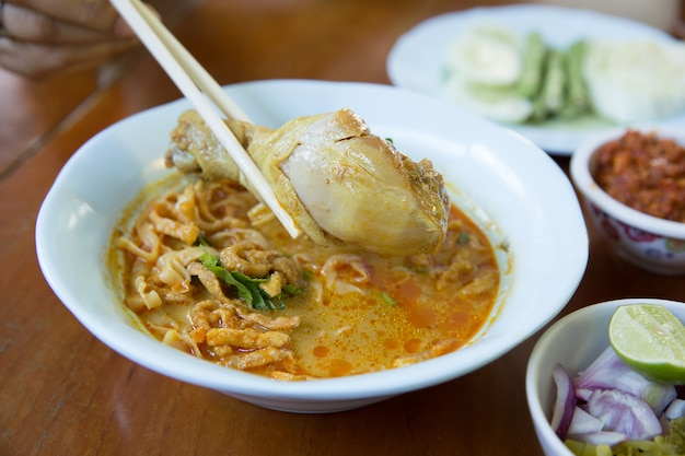 Khao soi, estilo tailandês do norte sopa de macarrão ao curry com frango em fundo de madeira