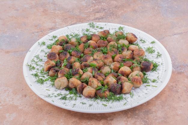 Khinkali caucasiano cozido em prato branco servido com ervas e especiarias.