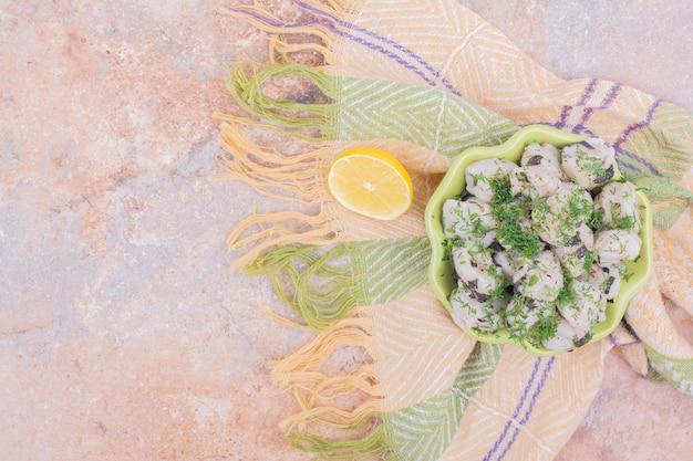Khinkali caucasiano cru com ervas picadas em uma tigela.