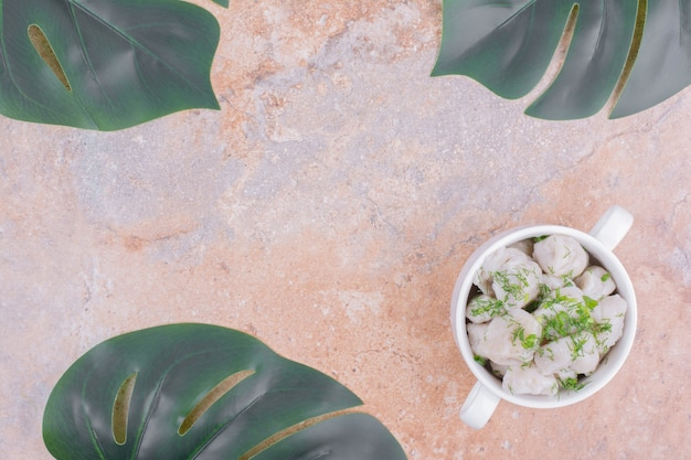 Khinkali caucasiano cru em uma tigela com ervas picadas