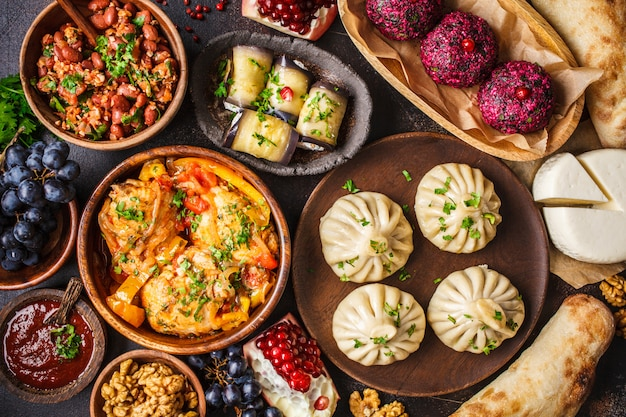 Khinkali, phali, chakhokhbili, lobio, queijo, rolinhos de berinjela, mesa escura.