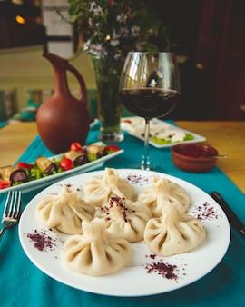 Khinkali servido com pãezinhos de berinjela e copo de vinho