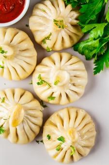 Khinkali tradicional georgian das bolinhas de massa com carne e verdes em um prato branco, vista superior.