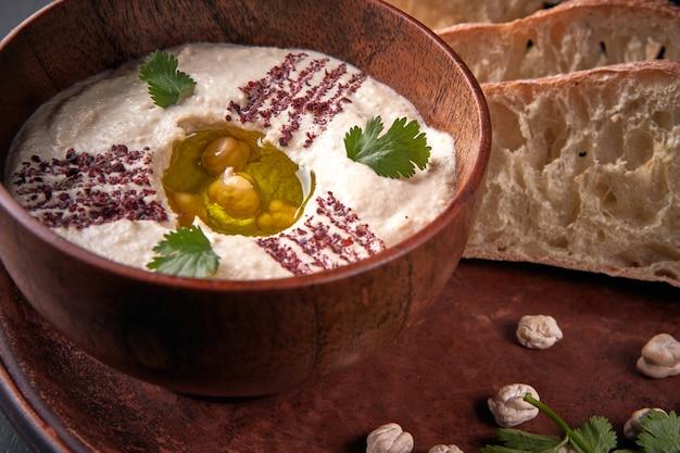 Khumus com pão em um prato de barro