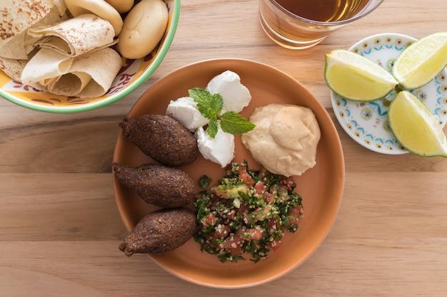 Kibbeh (trigo de bulgur / bola de carne), labneh, hummus e tabouleh e tigela com pão.