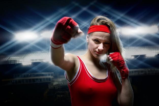 Kickboxer feminina em bandagens de boxe e roupas esportivas