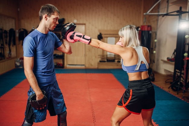 Kickboxer feminina em treino com personal trainer