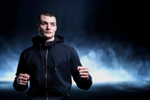 Kickboxer jovem posando no estúdio. o conceito de artes marciais, publicidade de roupas esportivas, nutrição esportiva. mídia mista