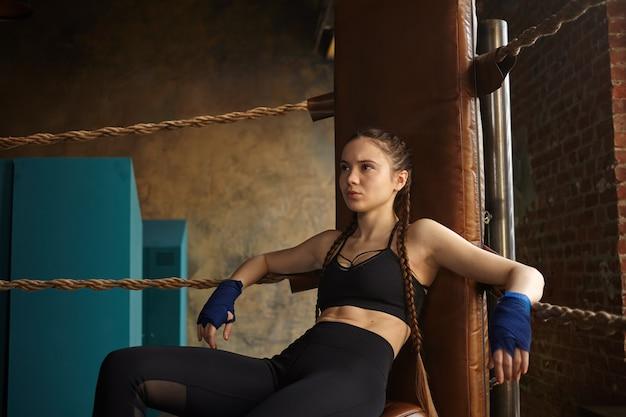 Kickboxer jovem profissional séria, vestindo roupas esportivas da moda e bandagens nas mãos, descansando após o treino