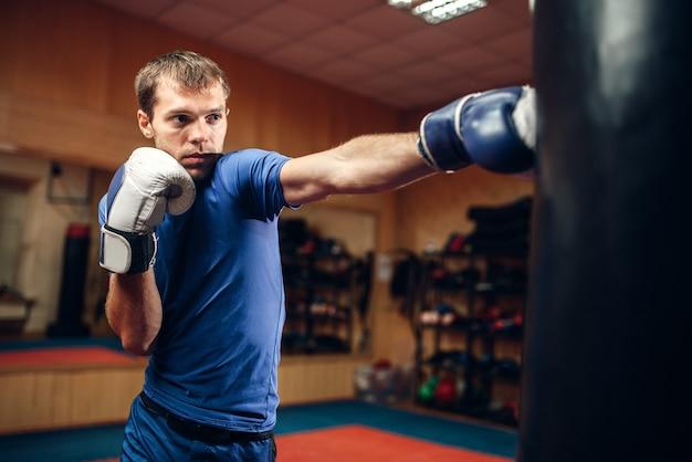Kickboxer masculino atinge o saco de pancadas no treino no ginásio. boxeador praticando golpes no treinamento, prática de kickboxing