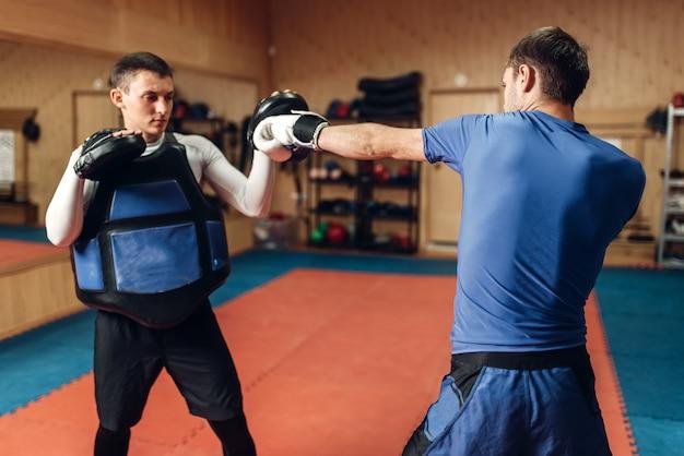 Kickboxer masculino em luvas praticando soco de mão com um personal trainer em almofadas, treino no ginásio. boxeador em treinamento, prática de kickboxing