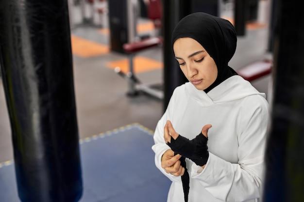 Kickboxer mulher árabe em hijab amarra uma bandagem elástica preta na mão antes de lutar e treinar na academia, sozinha
