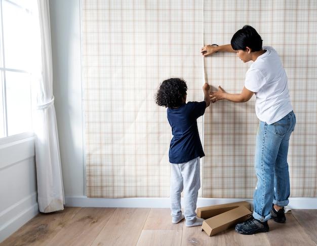 Kid ajudando a mãe a instalar o papel de parede