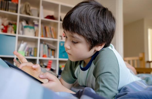 Kid auto-isolamento usando tablet para a lição de casa,