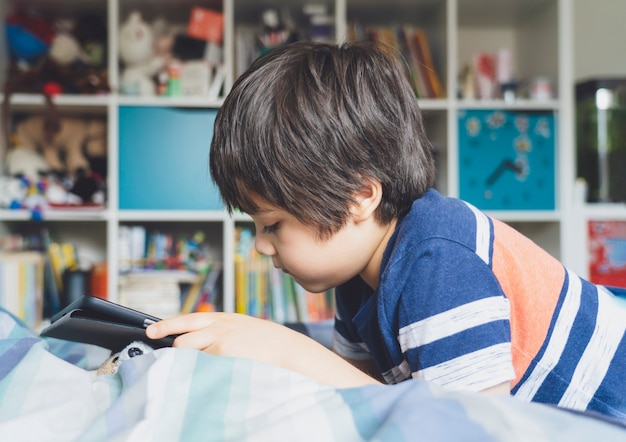 Kid auto-isolamento usando tablet para sua lição de casa, childlying na cama usando tablet digital, procurando informações na internet, educação em casa, distância social, educação on-line de e-learning