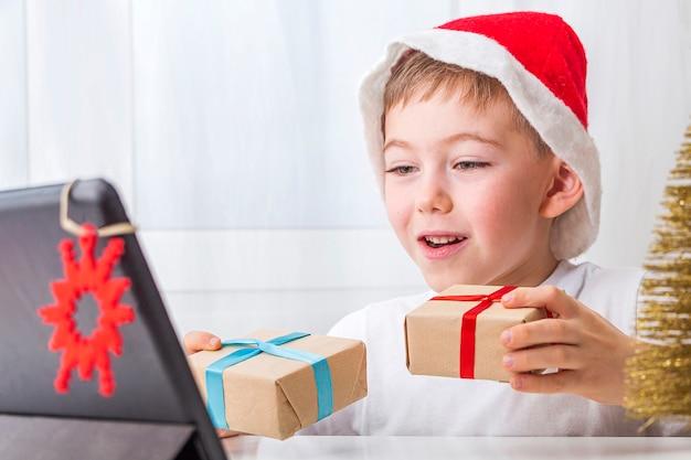 Kid boy comemora o natal online com amigos ou avós em videochamada no tablet