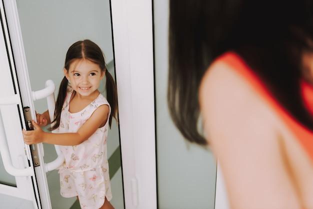 Kid brinca com a mãe abre a porta na clínica pediátrica