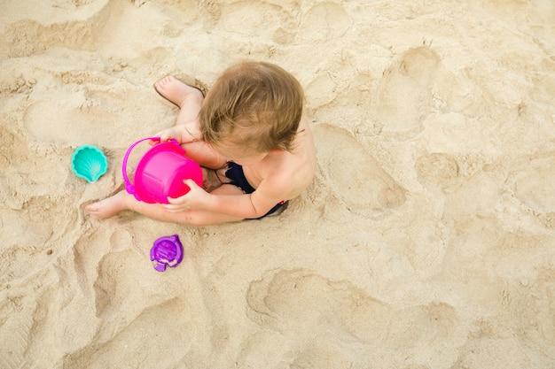 Kid brincando com brinquedos na areia