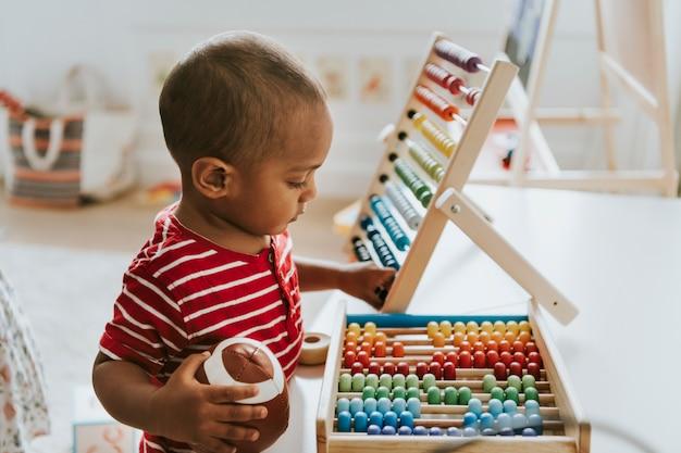 Kid brincando com um ábaco de madeira colorido