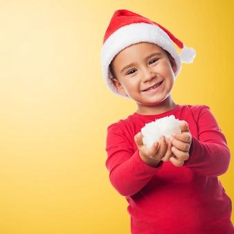 Kid com a neve em suas mãos